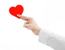 Heart Disease and Health Topic: hand doctor in a white shirt holding a card in the form of a red heart isolated Stock Photography