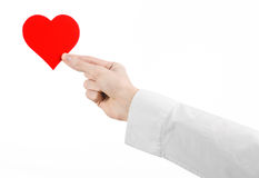 Heart Disease and Health Topic: hand doctor in a white shirt holding a card in the form of a red heart isolated Stock Photos
