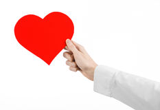 Heart Disease and Health Topic: hand doctor in a white shirt holding a card in the form of a red heart isolated Stock Images