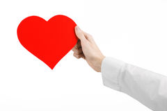 Heart Disease and Health Topic: hand doctor in a white shirt holding a card in the form of a red heart isolated Royalty Free Stock Images