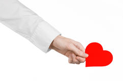 Heart Disease and Health Topic: hand doctor in a white shirt holding a card in the form of a red heart isolated Royalty Free Stock Image