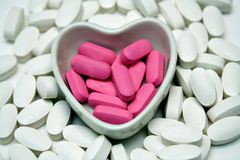 Heart dish of Pills. A heart shaped dish filled and surrounded by pills Stock Images