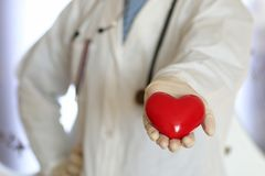 Heart in doctor hand. Hands in white gloves man dressed in a white robe doctor holding object royalty free stock images