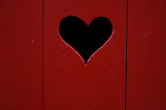 Heart in door. A wooden door painted in red with a heart cut out royalty free stock photography