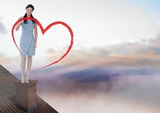 Heart drawing and Businesswoman standing on Roof with chimney and colorful sky Royalty Free Stock Image