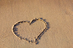 Heart drawing in the sand on the beach Stock Photography