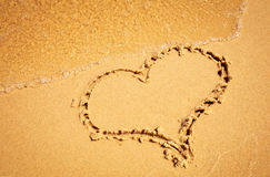 Heart drawing in the sand beach. Wave washes drawn in the sand Heart royalty free stock photography