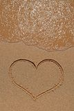 Heart drawing on sandy beach. Wave running over the sand beach with heart drawing stock photos