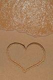 Heart drawing on sandy beach Stock Photos