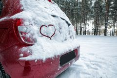 Heart drawing on snow covered car in winter forest. Space for text royalty free stock photos