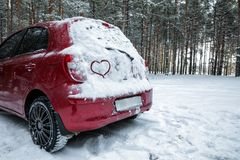 Heart drawing on snow covered car in winter forest. Space for text stock photos