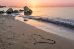Heart drawn on the beach sand. With sun above the horizon Stock Photography