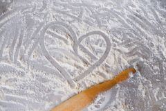 A heart drawn with a finger in scattered wheat flour on a light wooden table . Background with scattered flour. stock photography