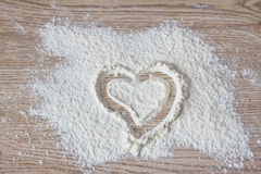 Heart drawn on flour. On the wooden table Royalty Free Stock Photo