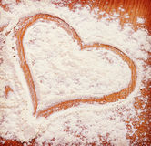 Heart drawn with flour on the kitchen table. Vintage retro hipst Royalty Free Stock Image