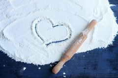 Heart drawn on flour on the table. There is a rolling pin near it. Concept of cooking with love stock photography