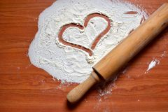 A heart drawn by flour on wooden table. A heart drawn by flour and wooden dough roller on the brown wooden table background Royalty Free Stock Images