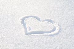 Heart drawn on the fresh white snow on a sunny day Stock Images