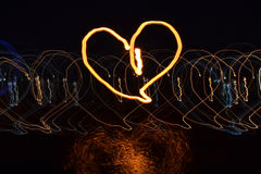 Heart drawn with light at night with long exposure on dark background and water reflexion Stock Photos