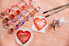 A heart drawn by lipstick, with more hearts made of powder and blush. 'Love makeup ' valentine card with a professional brush. Colored paints and brushes royalty free stock photo
