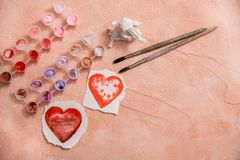 A heart drawn by lipstick, with more hearts made of powder and blush. 'Love makeup ' valentine card with a professional brush. Colored paints and brushes royalty free stock image