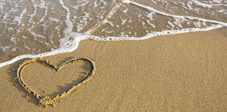 Heart drawn on ocean beach sand. Romantic. Royalty Free Stock Photography