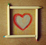 Heart drawn on paper in a frame from colored wooden pencils. Royalty Free Stock Photo