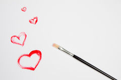 Heart drawn with red paint on white sheet of paper. And brush. Drawing for Valentine`s Day. Space for your text Royalty Free Stock Photos