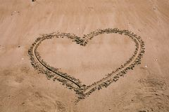 Heart drawn in the sand. Beach background with heart drawing. Heart shape love symbol as background. Love concept royalty free stock images