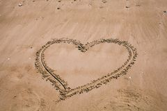 Heart drawn in the sand. Beach background with heart drawing. Heart shape love symbol as background. Love concept stock images