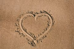 Heart drawn in the sand. Beach background with heart drawing. Heart shape love symbol as background. Love concept stock image