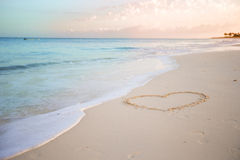 Heart drawn in the sand. Beach background. Top view. Heart on sand and summer sea with sky Stock Photos