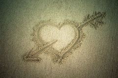 Heart drawn in the sand. Beach background. Top view. Tinted Royalty Free Stock Photo