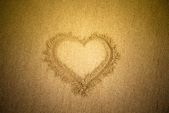 Heart drawn in the sand. Beach background. Top view. Tinted Stock Photos