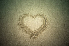 Heart drawn in the sand. Beach background. Top view. Tinted Royalty Free Stock Photography