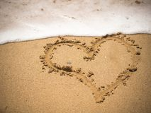 heart drawn in the sand stock image
