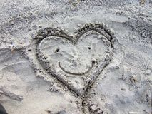 Heart drawn in the sand. At beach, with smiley face stock photography