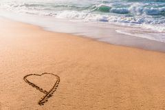 Heart drawn in the sand on the beach at sunset. With waves washing in royalty free stock photos