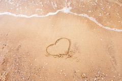 Heart drawn on a sand of beach with the wave of the sea. Free space for your text. Summer holiday concept. Romantic love Royalty Free Stock Images
