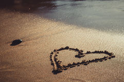 Heart drawn on sand sea beach. Closeup toned photo of heart drawn on sand sea beach Royalty Free Stock Image