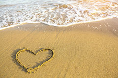 Heart drawn on the sand of a Sea beach. Soft wave in a sunny day Royalty Free Stock Photos