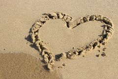Heart drawn on sand and sea, view from above stock photos