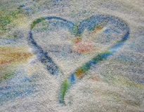 Heart drawn in sand. Heart drawn in sparkling sand with a colorful backround royalty free stock image