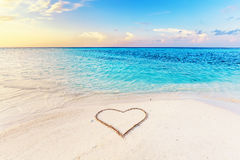 Heart drawn on sand of a tropical beach at sunset. Clear turquoise ocean. Maldives islands Stock Images