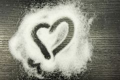 Heart drawn on scattered sugar. Heart drawn on scattered sugar on a wooden background Stock Photos