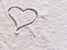 Heart drawn in the snow as a background for postcard. Stock Photos