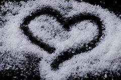 Heart drawn with snow on black background stock photo