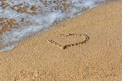 Heart drawn on wet sand beach. Part of the heart is washed away by a wave. Symbol of the beginning or the end of love royalty free stock images