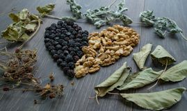 Heart of dried cherries, nuts and dried leaves of tea. Side view Stock Photos