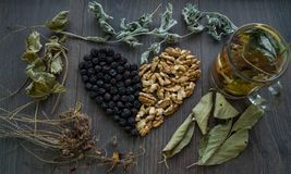 Heart of dried cherries, nuts and dried leaves of tea , top view. Heart of dried cherries, nuts and dried leaves of tea on the window , cup of herbal tea Royalty Free Stock Images